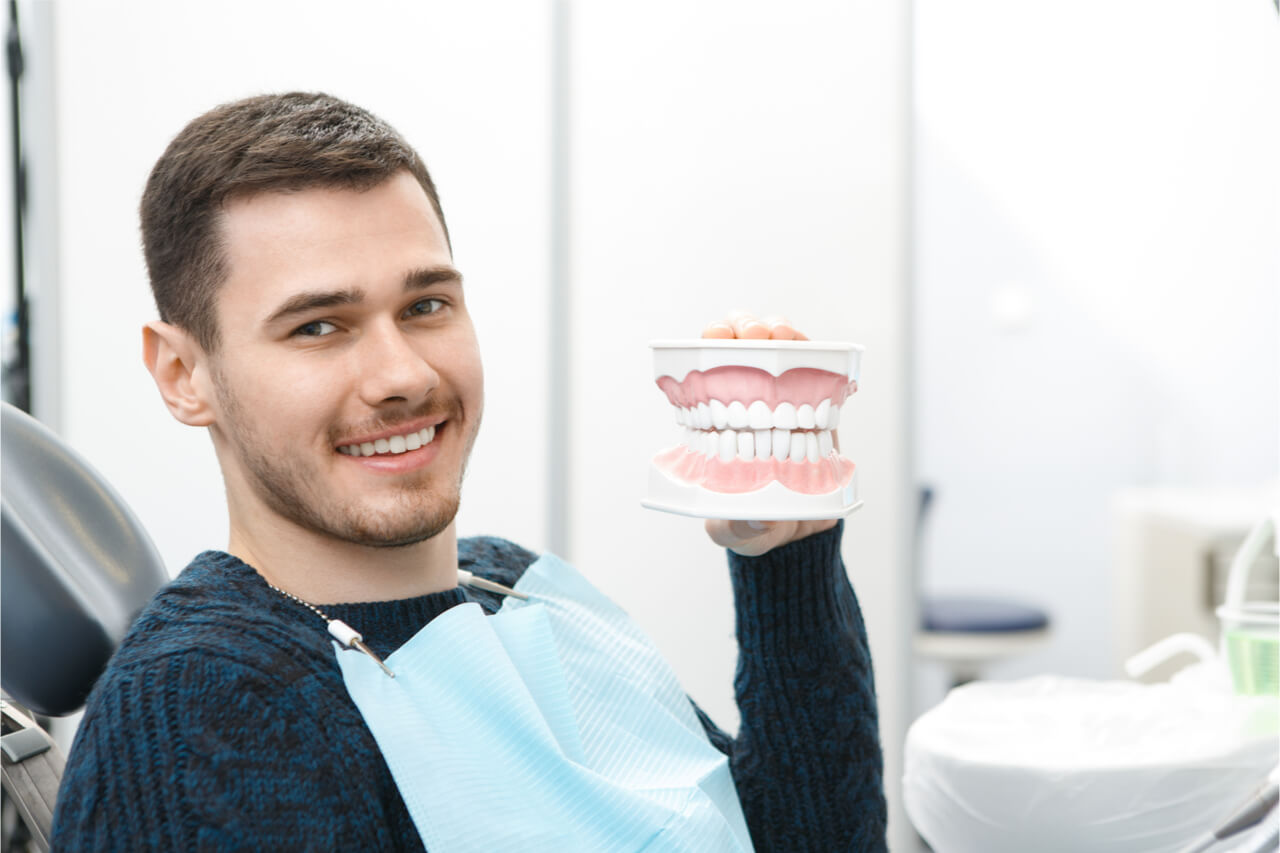 The patient holds an artificial teeth model.